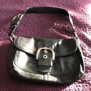 Black leather coach buckle bag.